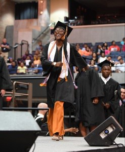 Female graduate walks across the stage