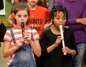 elementary students playing the recorders at a winter concert.