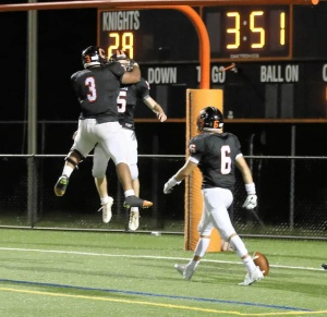 Football players leaping in air celebrating a play near goal posts.