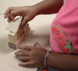 girls hands building with blocks
