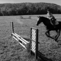 Student photograph of a girl jumping a gate on a horse