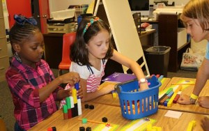 Girls doing a math activity with blocks