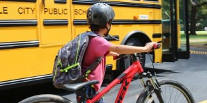 Student with bike near bus