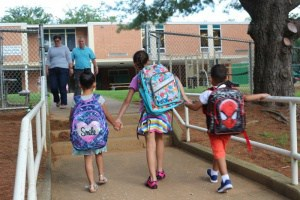 children holding hands as they walk into the Greenbrier Elementary School building
