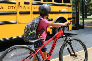 young boy with a helmet walking a bike he has ridden to school
