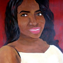 portrait of a smiling African-American young woman wearing white agains a dark red background
