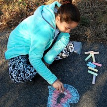 photograph of a young girl drawing on the sidewalk with chalk