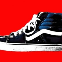 photograph of a black sneaker on a red background