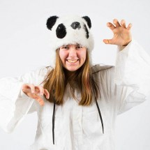 portrait photograph of a girl dressed in white with a panda hat on