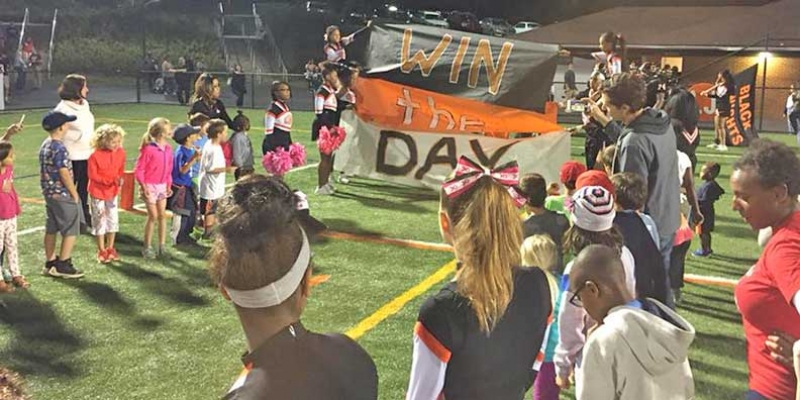 Burnley-Moran sponsored the All-Elementary tailgate before the CHS football game. Students make tunnel and hold banner for football players.