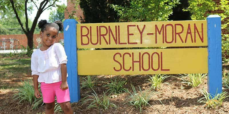 Child poses beside the Burnley-Moran School sign.