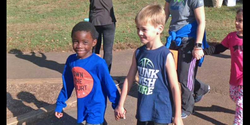 Boys holding hands participating in the Walk-a-Thon.