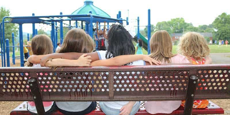 Children linking arms on playground bench.