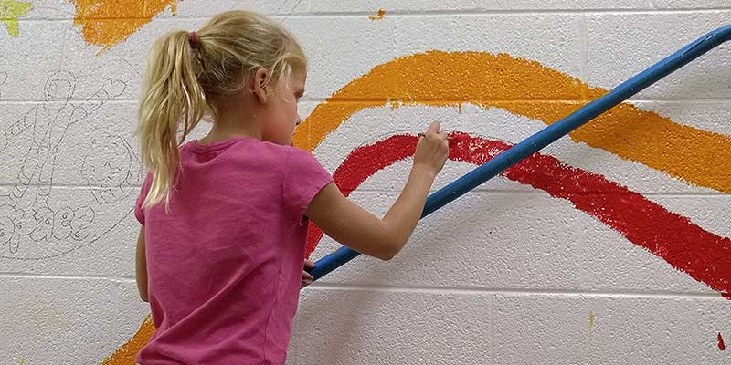 Girl works on Burnley-Moran wall mural painting project.
