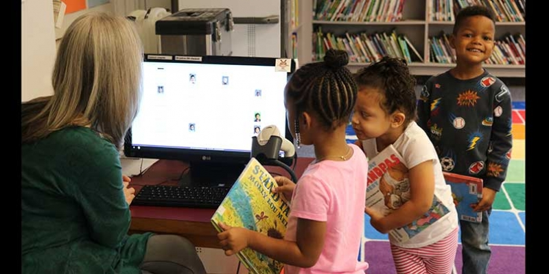 Students check out books during library time.