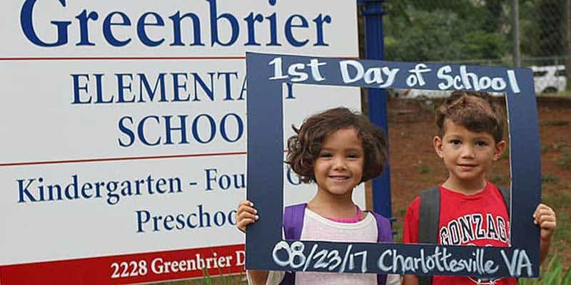 First day of school picture of siblings beside the school sign.
