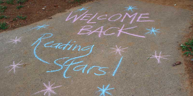 Sidewalk chalk art welcoming students back to school.