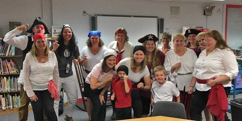 Teachers and students pose in pirate costumes for Shiver Me Letters and Numbers night.