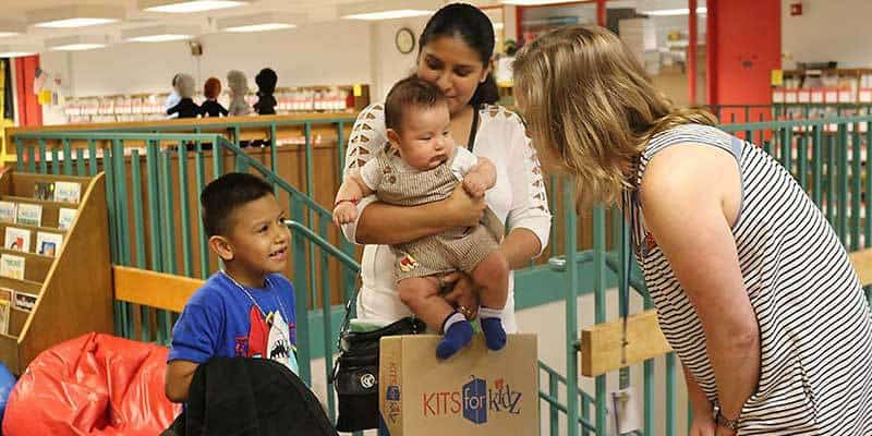 Teacher greets family at Back-to-School Night