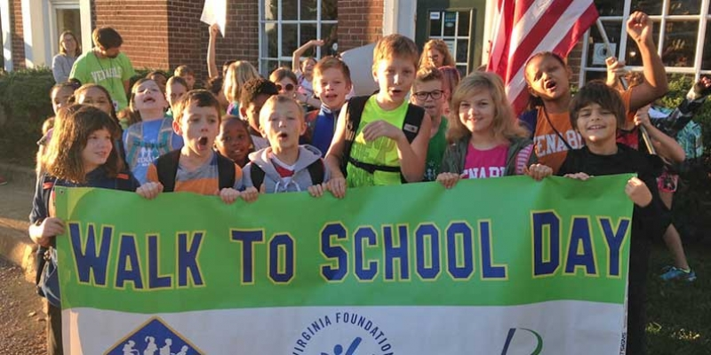 Students pose with banner for Walk to School Day.