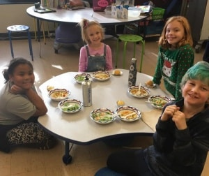 Students enjoying homemade stone soup and salad.