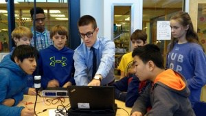 Brendan Martin with a group of students looking at computer and circuitry