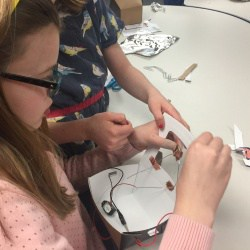 Girls creating a circuit for a door alarm on a box