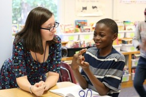 Johnson teacher sitting with student.