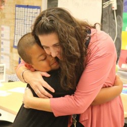 Teacher hugs child at elementary school open house.