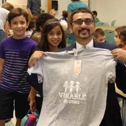 Secretary Qarni receives tshirt from two Venable students