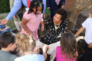 Dr. Atkins with children in garden petting a goat.