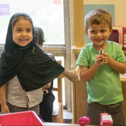 two elementary students, boy and girl, playing in classroom.