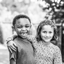Photograph of two children with arms around eachother.