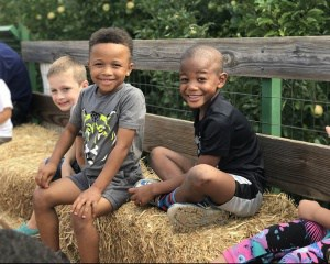 Photograph of three children on a hayride at apple orchard.