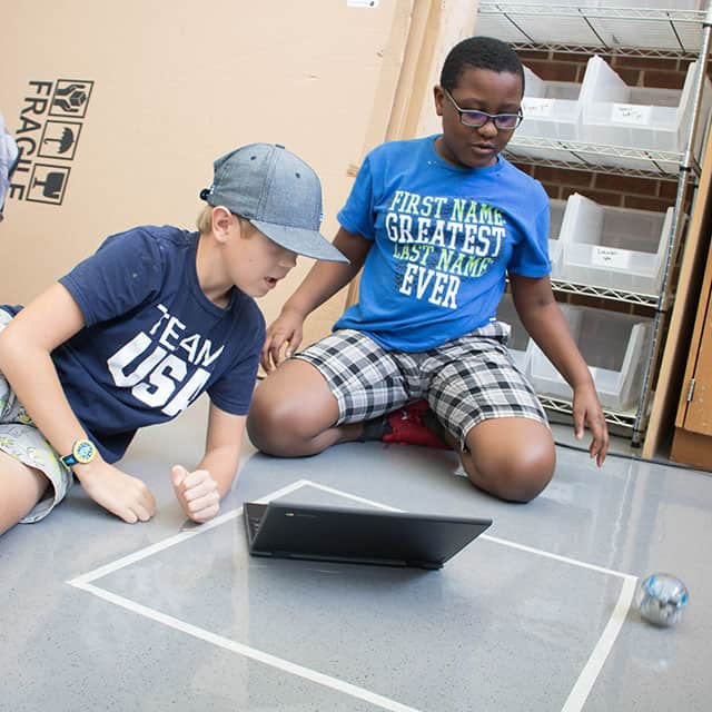 Two boys working with a lap top and Spheros.