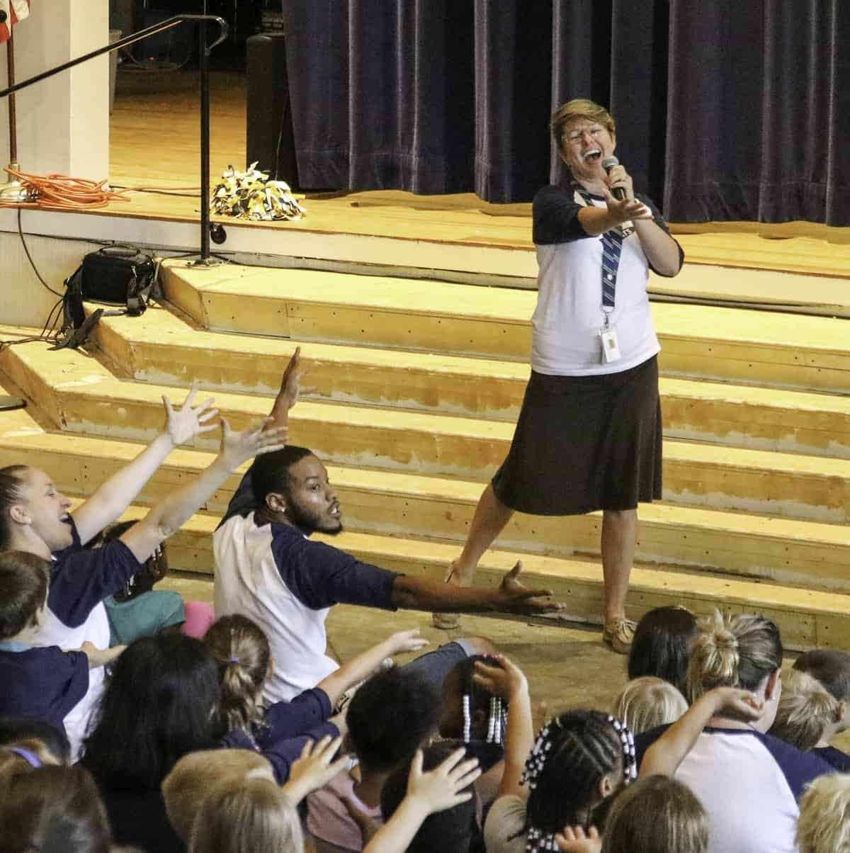 Teacher sings on stage at BME school-wide morning meeting.