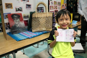 Student holds passport and features his project on Burma.