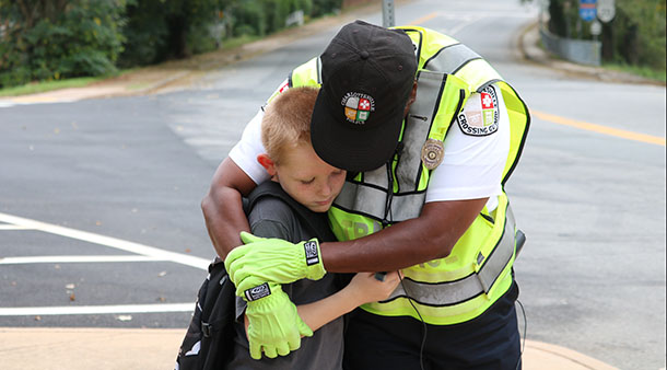 Crossing guard Miss Ruth hugs a Clark student
