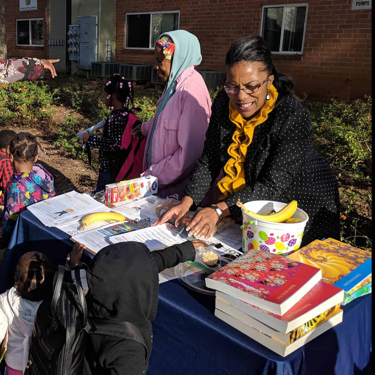 Family engagement coordinator distributes books and snacks to children at bus stop.