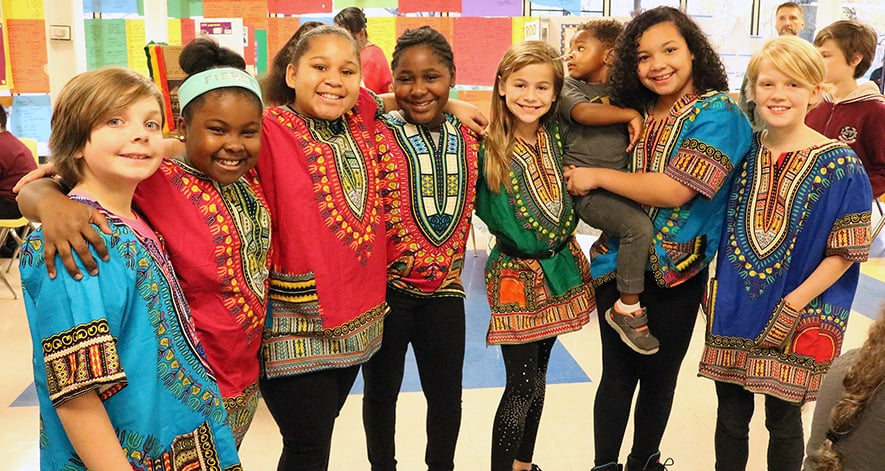 Student dancers wearing colorful tunics at Walker International Day.