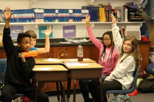 Students raising hands during participatory budgeting discussion