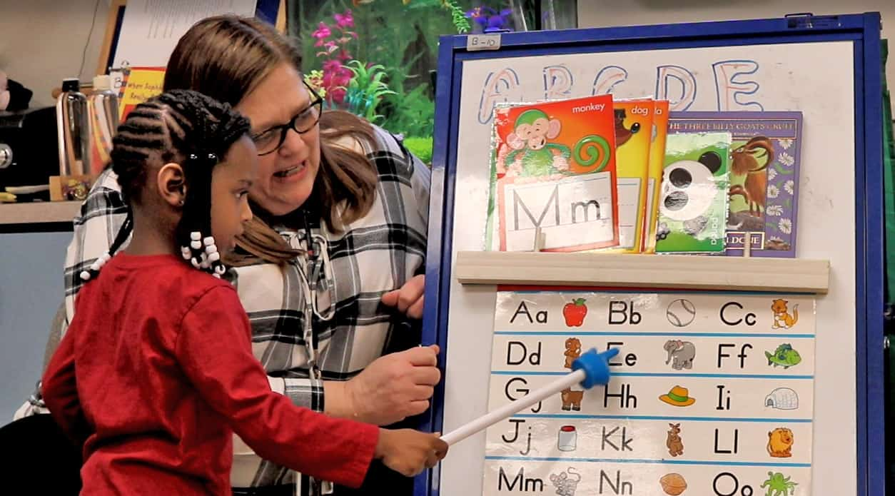 Teacher helps students point to ABC's on chart.