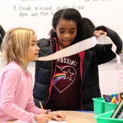 Elementary students work on a measuring activity.