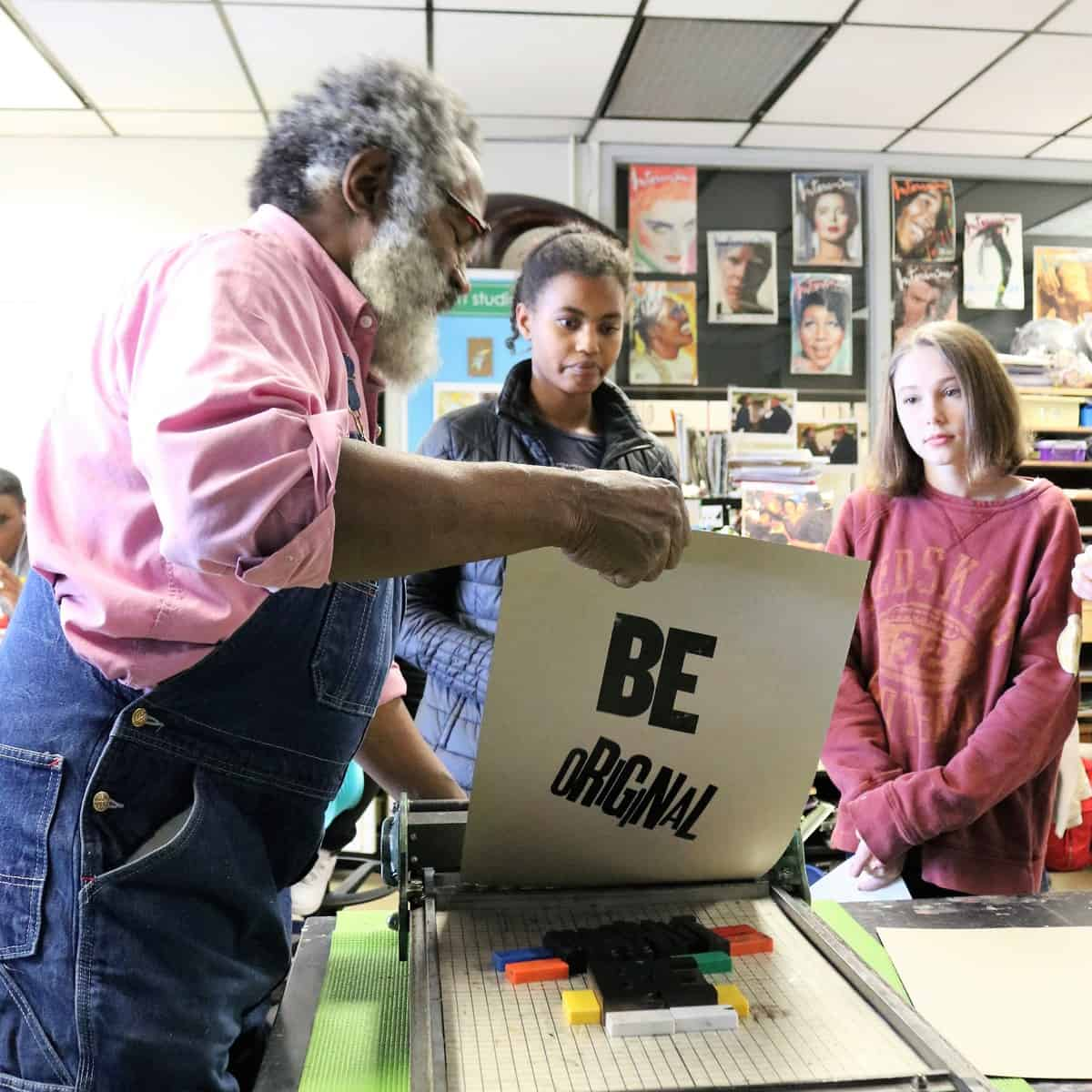 Printer Amos Paul Kennedy, Jr. shows CHS students how to make a letterpress print.