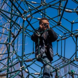 Student taking photo while climbing on playground equipment.