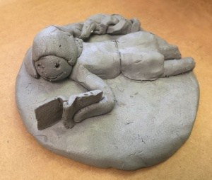 clay statue of girl reading
