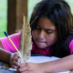 Girl holds feather while writing.