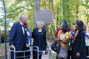 Eugene Williams, wife, and daughters stand at newly-installed plaque at Johnson Elementary.