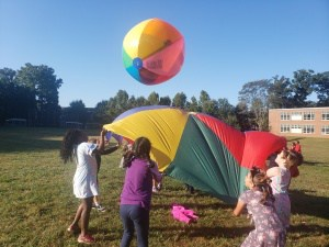 Johnson PE Class plays with parachute and ball.