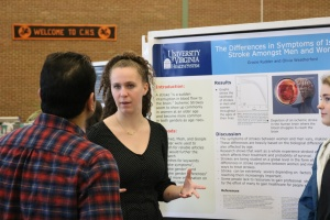Two female students present poster to judge.
